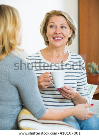 Senior woman and young girl talking and drinking tea - stock photo