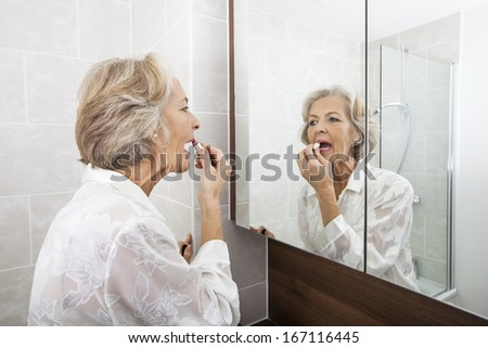 Senior woman applying lipstick while looking at mirror in bathroom - stock photo