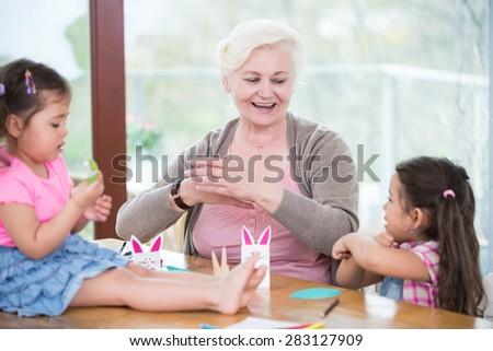 Senior woman assisting granddaughters in art work at home - stock photo