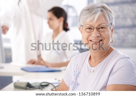 Senior woman at doctor's room waiting for examination. - stock photo
