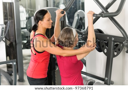 Senior woman at fitness center exercise shoulder with personal trainer