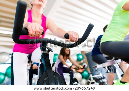 Senior Woman at Fitness Spinning on bike in gym, shot from a low angle - stock photo