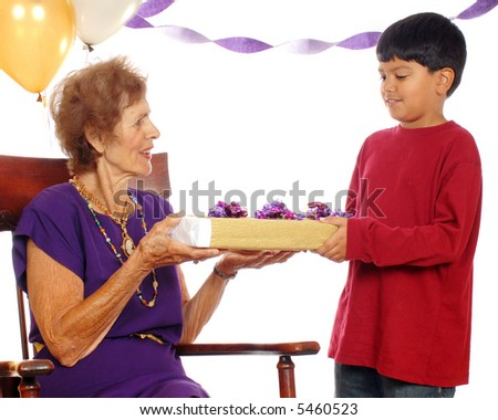 Senior woman at her birthday party, accepting a gift from her great grandson. - stock photo