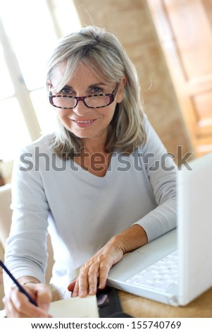 Senior woman at home figuring out income tax