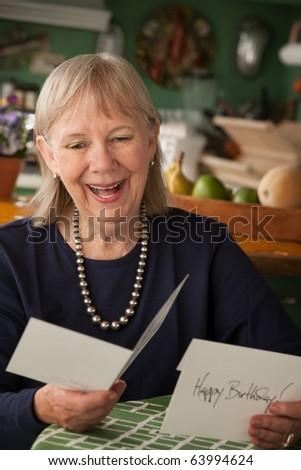 Senior woman at home reading greeting card - stock photo