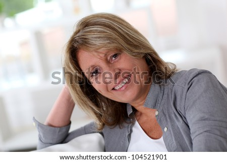 Senior woman at home sitting in sofa - stock photo