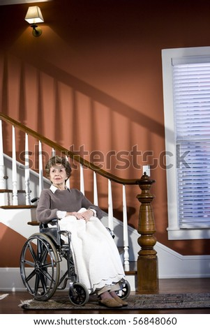 Senior woman at home sitting in wheelchair alone - stock photo
