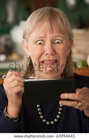 Senior woman at home with checkbook - stock photo