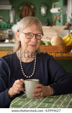 Senior woman at home with coffee or tea