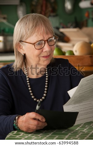 Senior woman at home with many bills - stock photo