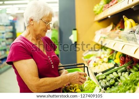 Senior woman at supermarket - stock photo