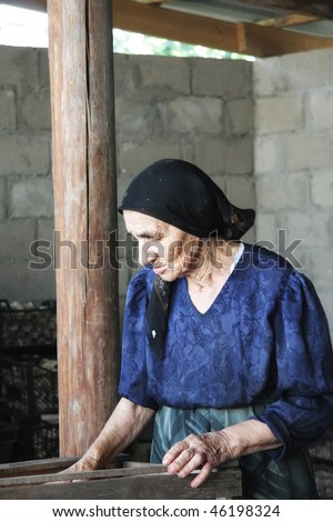 Senior woman at work in yard covered with roof side-view