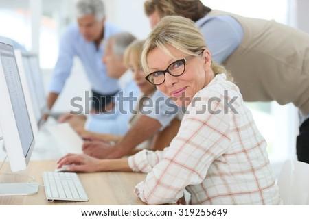Senior woman attending training business class - stock photo