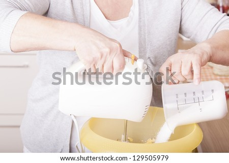 senior woman baking homemade chocolate cake,using a mixer and milk. baking chocolate/stracciatella cake in a glass jar.