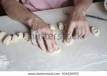 Senior woman baking pies in her home kitchen. Cutting out circles from raw dough.female hands crumple pieces of dough, shaped - stock photo