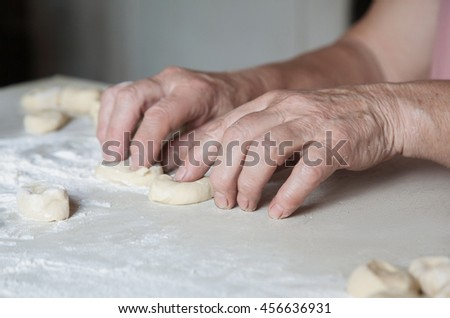 Senior woman baking pies in her home kitchen.female hands crumple pieces of dough, shaped - stock photo