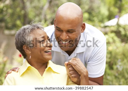 Senior Woman Being Hugged By Adult Son