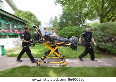 Senior woman being rush to hospital by ambulance staff - stock photo