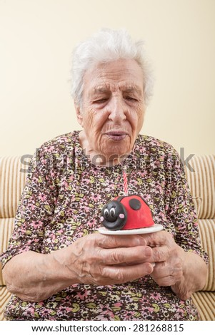 senior woman blowing birthday cake's candle - stock photo