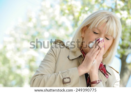 Senior woman blowing her nose outdoor - stock photo