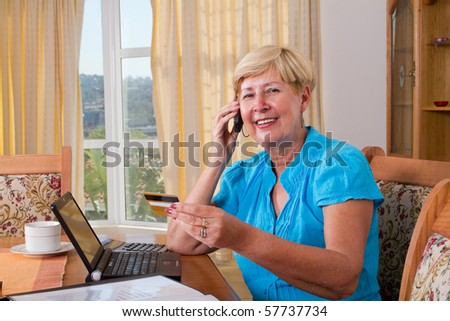 senior woman buying online and paying with credit card - stock photo