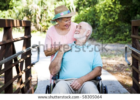 Senior woman caring for her disabled husband in his wheelchair. - stock photo