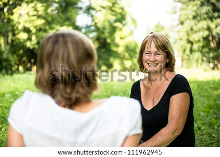 Senior woman chatting with her adult daughter outdoor in nature - stock photo