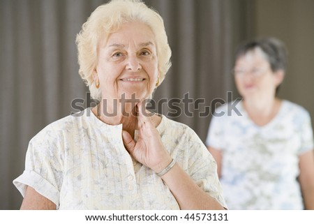 Senior woman checking her pulse after exercising in a gym - stock photo