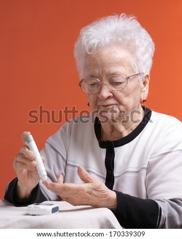 Senior woman checking sugar level - stock photo