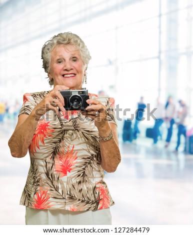 Senior Woman Clicking Photo, Indoors - stock photo