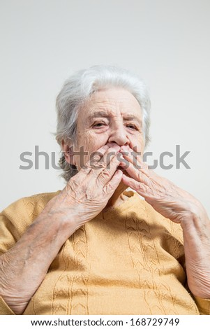 senior woman closing her mouth wit her wrinkled hands