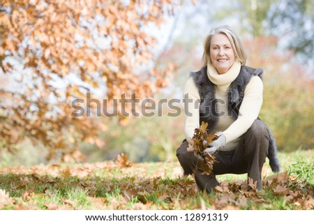 Senior woman collecting autumn leaves on walk - stock photo