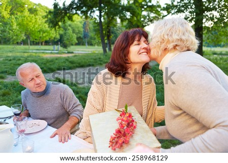 Senior woman congratulates friend at birthday party with a gift - stock photo