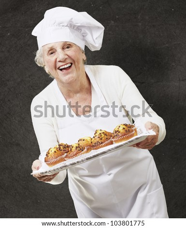 senior woman cook holding a tray with muffins against a black background - stock photo