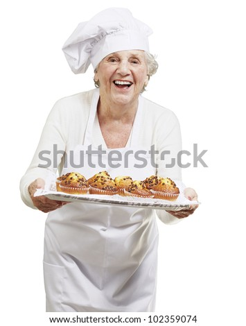 senior woman cook holding a tray with muffins against a white background