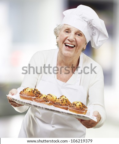 senior woman cook holding a tray with muffins, indoor - stock photo