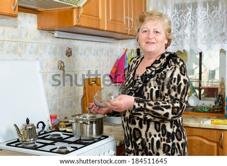 Senior woman cooking at the kitchen - stock photo