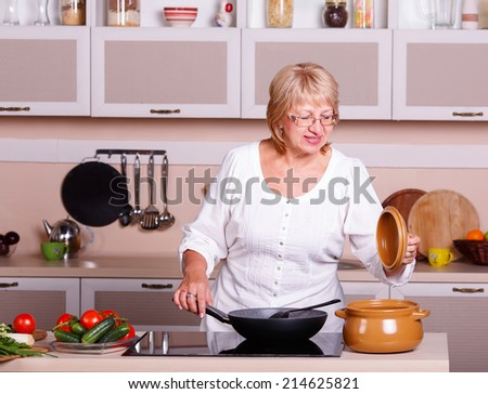 Senior woman cooking in the kitchen. Healthy food. Diet concept. Healthy lifestyle. Cooking at home. Cook meals at home. Woman fries and cooks in kitchen utensils in the kitchen. pots, pans, stove.