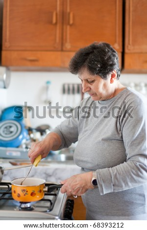 Senior woman cooking on a stove in bright daylight - stock photo