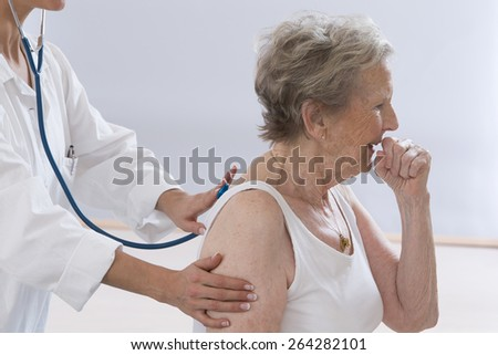 Senior woman coughing while doctor examining her - stock photo