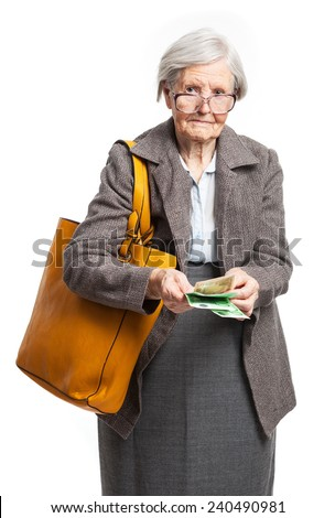 Senior woman counting money while standing over white background - stock photo