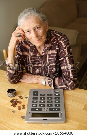 Senior woman counting money with calculator - stock photo
