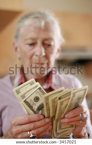 Senior woman counting savings money. Shallow DOF, focus on hands. - stock photo