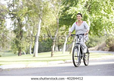 Senior Woman Cycling In Park - stock photo