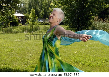 Senior woman dances in the backyard. - stock photo