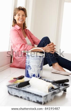 Senior woman decorating house - stock photo