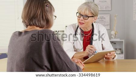 Senior woman doctor tablet talking patient - stock photo