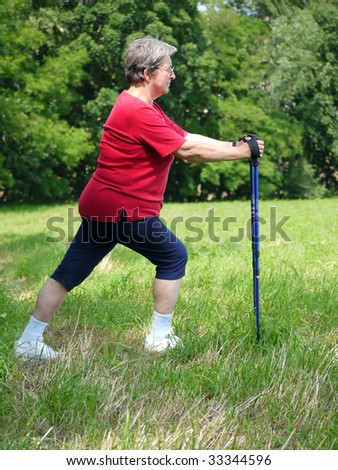 Senior woman doing a series of warm-up exercises with walking poles - stock photo