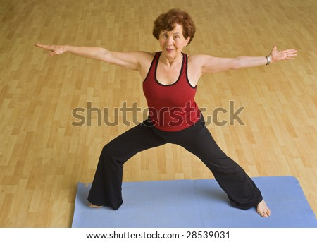 senior woman doing bikram hot  yoga in a gym