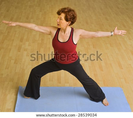 senior woman doing bikram hot  yoga in a gym - stock photo